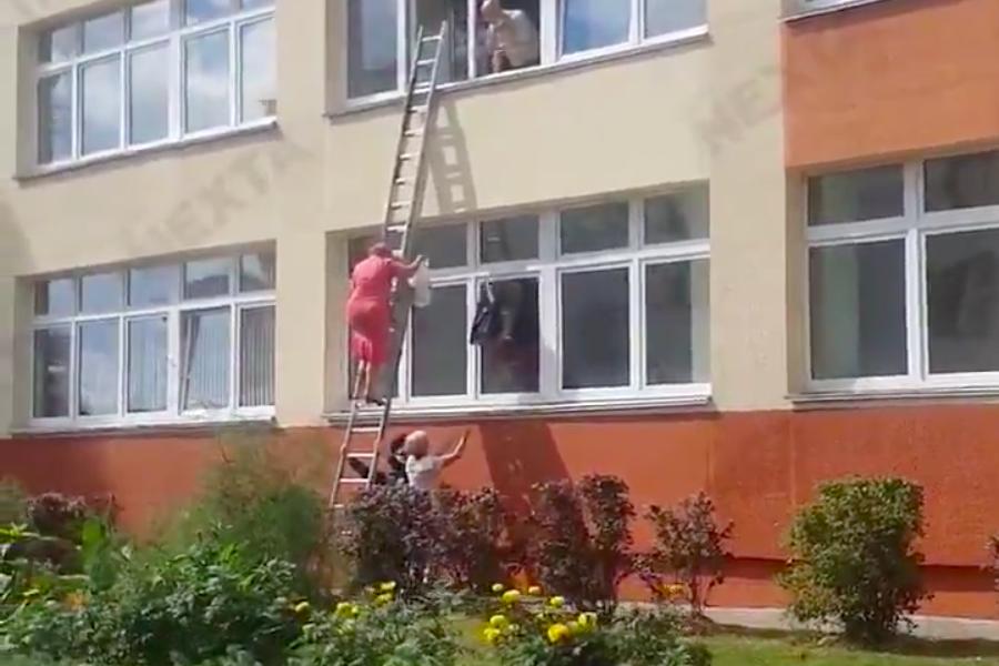Відео. У Мінську жінка з комісії через вікно спускала пакет з бюлетенями
